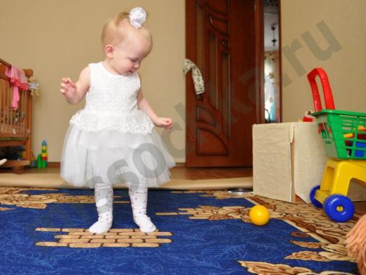 годовалая девочка в белом платье ходит по синему ковру