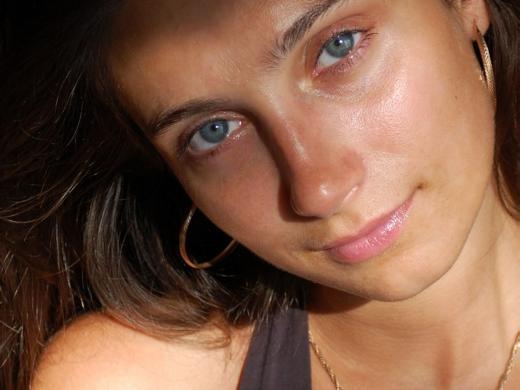 красивая девушка с тёмными волосами и голубыми глазами смотрит на вас