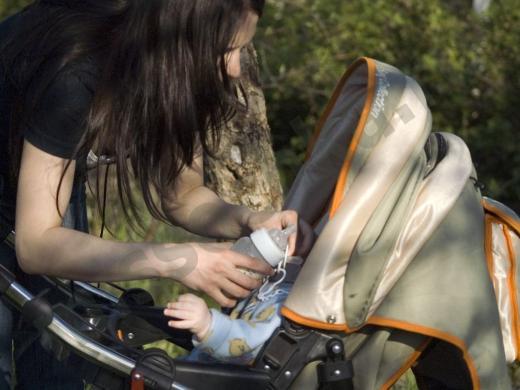 мать протягивает ребёнку бутылочку со смесью
