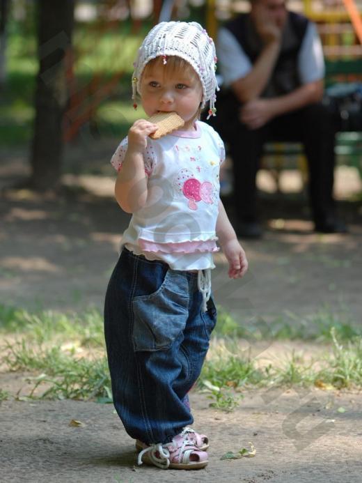 маленькая девочка летом на улице ест печенье